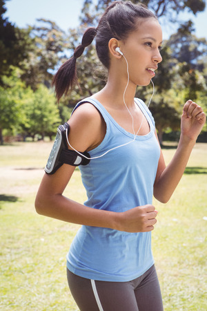 Fit woman jogging in the park on a sunny day photo