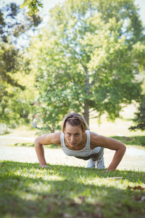 plank position: Fit woman in plank position on a sunny day