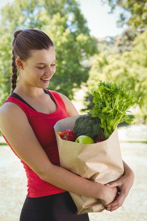 mujer alegre: Ajustar la mujer que sostiene bolsa de alimentos sanos en un día soleado