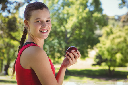 woman holding bag: Fit woman holding bag of healthy groceries on a sunny day Stock Photo