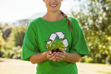 activist: Environmental activist showing a plant on a sunny day
