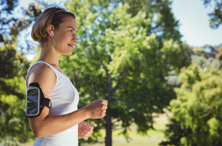 slim woman: Fit woman jogging in the park on a sunny day Stock Photo