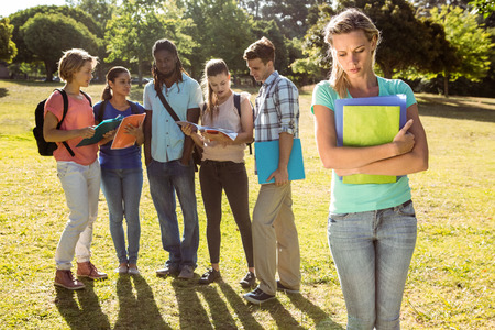 peer pressure: Student being bullied by a group of students on a sunny day