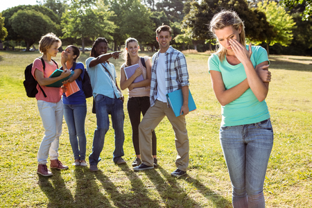 friendless: Student being bullied by a group of students on a sunny day