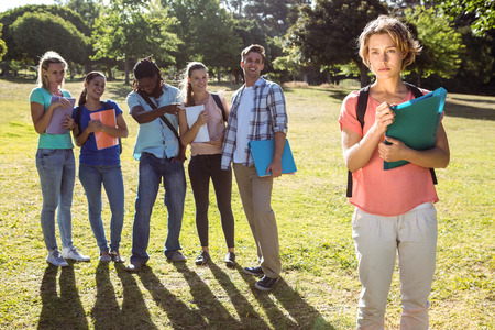 bullied: Student being bullied by a group of students on a sunny day