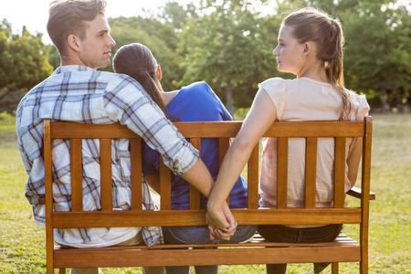dumped: Man being unfaithful in the park on a sunny day Stock Photo