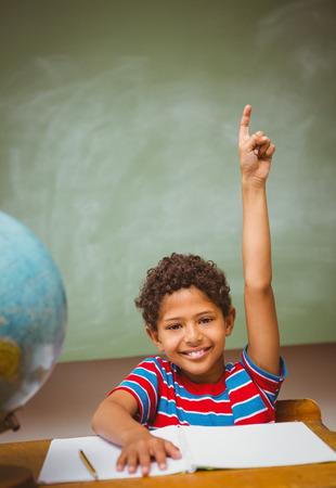 multiracial children: Portrait of cute little boy raising hand in classroom