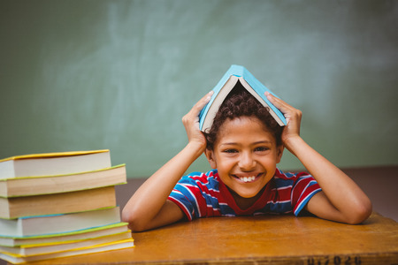 child studying: Portrait of cute little boy holding book over head in classroom Stock Photo
