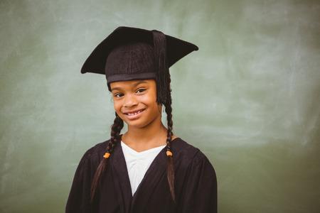 black graduate: Portrait of cute little girl wearing graduation robe