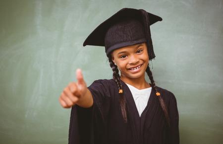 birrete de graduacion: Retrato de la ni�a linda en traje de graduaci�n que gesticula los pulgares para arriba