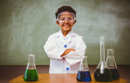 children learning: Portrait of cute boy with conical flasks in the classroom