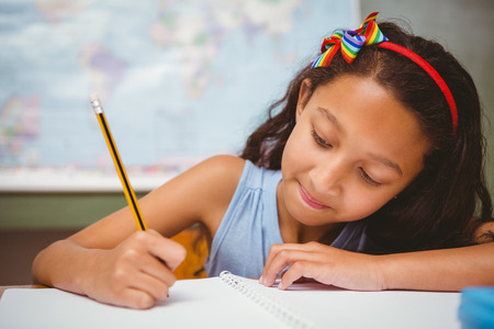 children writing: Portrait of cute little girl writing book in classroom