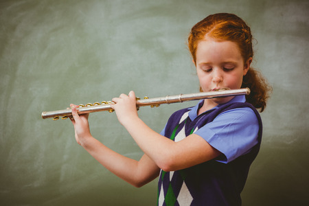 salon de clases: Retrato de la ni�a linda que toca la flauta en el aula Foto de archivo