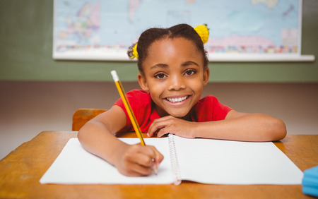 smiling girl: Portrait of cute little girl writing book in classroom