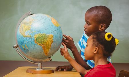 Vista lateral de los niños pequeños apuntando al mundo en el aula