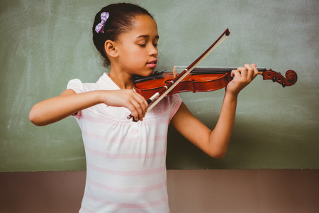 music education: Portrait of cute little girl playing violin in classroom