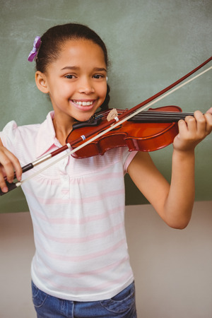 niños jugando en la escuela: Retrato de la niña linda que toca el violín en el aula