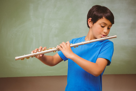Portrait of cute little boy playing flute in classroom