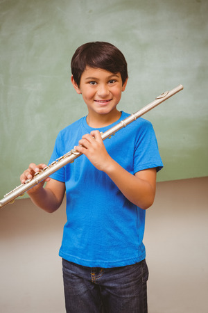 flute music: Portrait of cute little boy playing flute in classroom