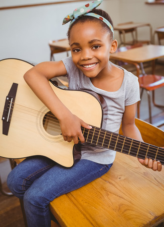 musical instrument: Portrait of cute little girl playing guitar in classroom Stock Photo