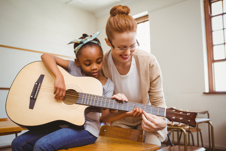 female teacher: Portrait of teacher teaching cute little girl to play guitar in classroom