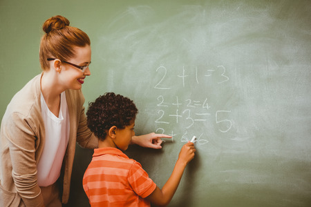 Rear view of teacher assisting little boy to write on blackboard in the classroom photo