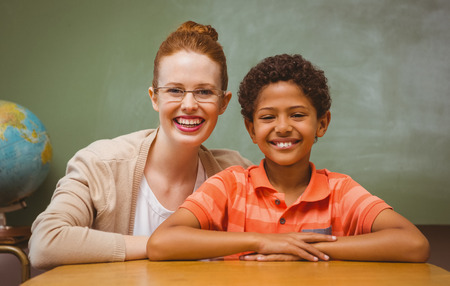 Portrait of happy female teacher and little boy in the classroom photo