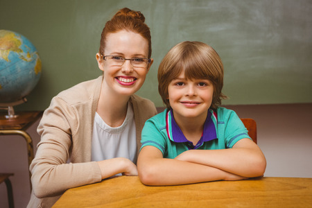 Portrait of happy female teacher and little boy in the classroom