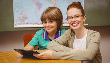 Portrait of female teacher and boy using digital tablet in the classroom photo