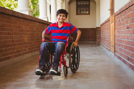 Portrait of cute little boy sitting in wheelchair in school corridor Фото со стока
