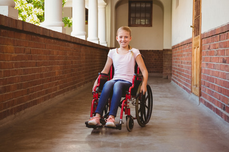 personas discapacitadas: Retrato de la niña linda que se sienta en la silla de ruedas en el pasillo de la escuela