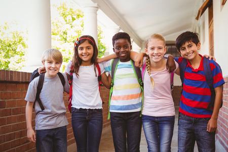elementary student: Portrait of smiling little school kids in school corridor