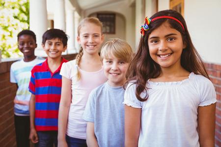 školní děti: Portrét usmívající se malé školní děti ve školní chodbě Reklamní fotografie