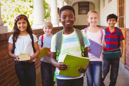 estudiante: Retrato de la sonrisa peque�os ni�os de la escuela en el pasillo de la escuela