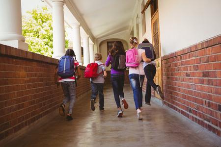 school bag: Vista posterior de cuerpo entero de niños de la escuela corriendo en el pasillo de la escuela