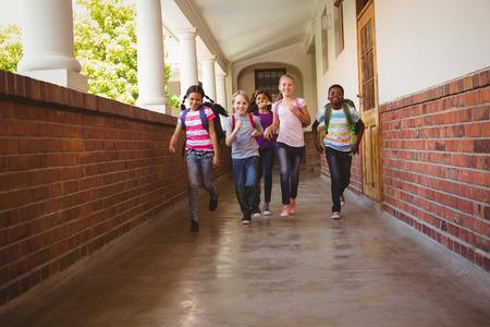 corriendo: Retrato de cuerpo entero de ni�os de la escuela corriendo en el pasillo de la escuela