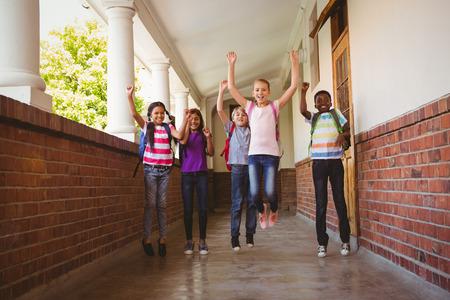 niño escuela: Retrato de cuerpo entero de niños de la escuela corriendo en el pasillo de la escuela