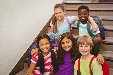 niños en la escuela: Retrato de niños de la escuela que se sienta en las escaleras en la escuela