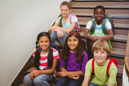Portrait of children sitting on stairs in the school