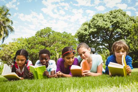 草の上に横たわると、公園で読書の子供の肖像