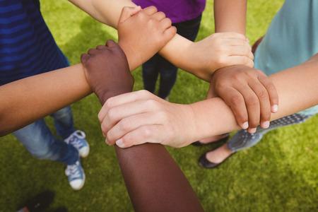 holding hands: Close up de los ni�os tomados de la mano juntos en el parque