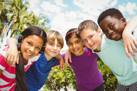 huddle: Portrait of happy children forming huddle at the park Stock Photo