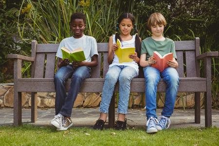 Portrait des enfants à lire des livres dans le parc