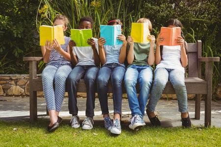 persona leyendo: Ni�os sentados en fila y la lectura de libros en el parque