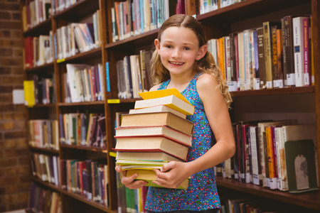 Portrait of cute little girl carrying books in the library photo