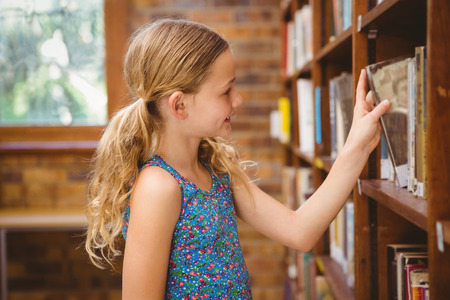 selecting: Cute little girl selecting book in library