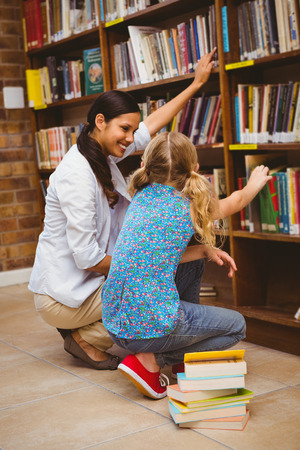Side view of teacher and little girl selecting book in the library photo