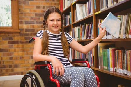ni�o discapacitado: Ni�a linda en el libro de la selecci�n de sillas de ruedas en la biblioteca