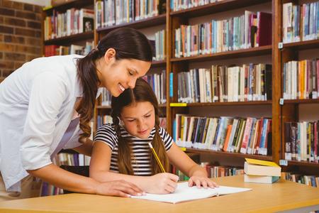maestro: Retrato del profesor ayudando ni�a con la tarea en la biblioteca