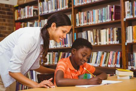 mujeres negras: Retrato del profesor ayudando ni�o con la tarea en la biblioteca
